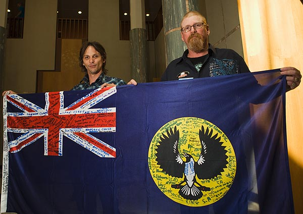 Sconey and Wayne Robert King holding the flag of Forgotten Australians South Australia Inc.